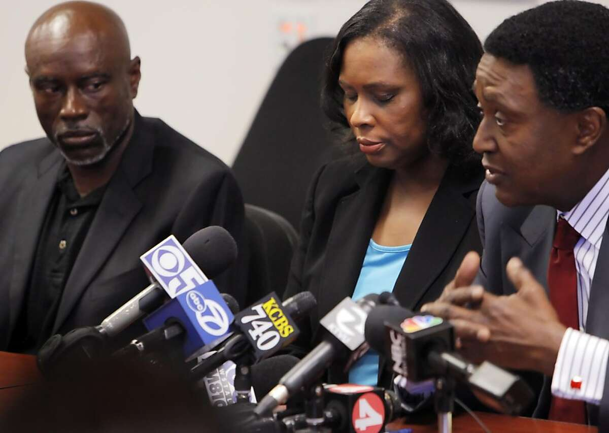 Wanda Johnson, center, mother of Oscar Grant, closes her eyes as she listens to her attorney, John Burris, right, tell the media about her settlement with BART, as her brother, Cephus Johnson, left, listens in. Johnson settled with BART over her son's shooting for $1.3 million on Tuesday, June 28, 2011. The settlement was announced at the office of her lawyer, John Burris, in Oakland, Calif.