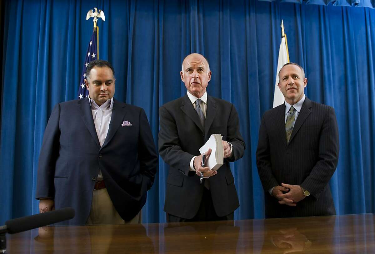 Gov. Jerry Brown, gets ready to sign the state budget surrounded by Assembly Speaker John A. Perez, D-Los Angeles, left, and Senate President Pro Tem Darrell Steinberg, D-Sacramento, on Thursday, June 30, 2011 at the state Capitol in Sacramento, Calif..