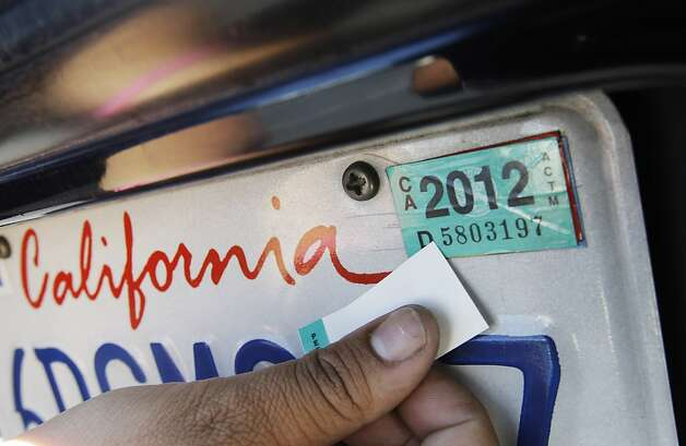 A woman puts new registration sticker on her car at a Department of Motor Vehicles office in Redwood City, Calif., Thursday, June 30, 2011. All Californians with a vehicle will pay $12 more a year to register it and millions of property owners who live outside cities will pay $150 a year for state fire protection. Those are among the new fees included in the state budget passed late Tuesday night without any Republican support. Photo: Paul Sakuma, AP