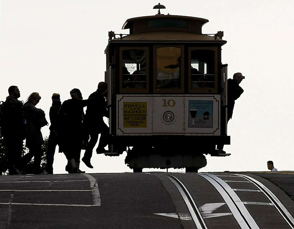 Cable car riders at the intersection of Powell and California Streets in San Francisco, Calif on Thursday January 28, 2010. With the Municipal Transportation Agency facing a $53 million budget deficit next year, they are considering the following recommendations: reduce the frequency of bus and rail service on most routes, equivalent to a 10 percent cut systemwide; charge Fast Pass users a premium for using express buses or cable cars; double the cost of discounted monthly passes for seniors, youth and the disabled to $30.