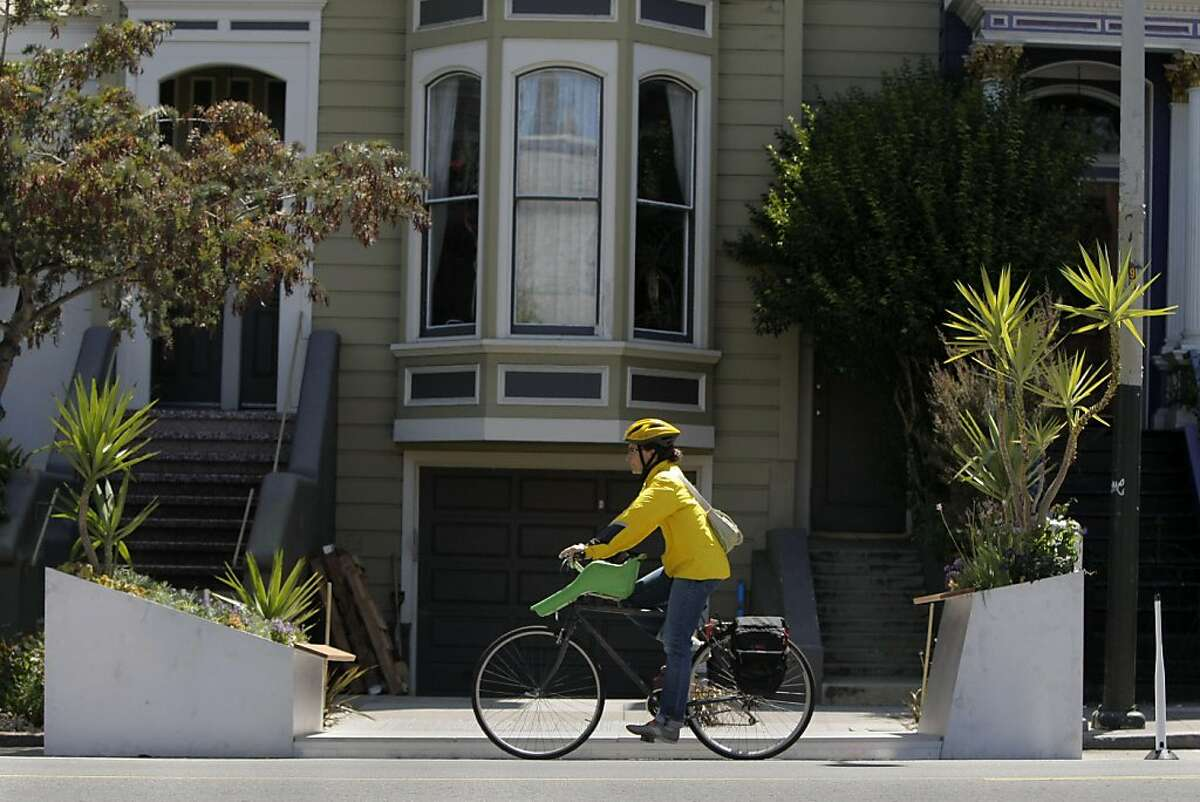 A woman rides her bike past a new parklet that is being finished at 937 Valencia in San Francisco Calif., on June 24, 2011.