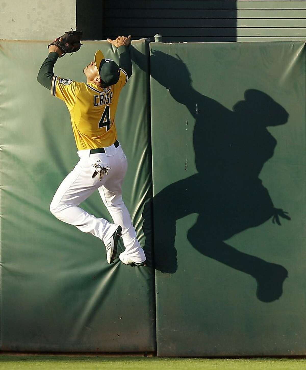 Oakland Athletics center fielder Coco Crisp climbs the wall, but is unable to catch a twor-un home run by Florida Marlins' Hanley Ramirez during the first inning of a baseball game Wednesday, June 29, 2011, in Oakland, Calif.
