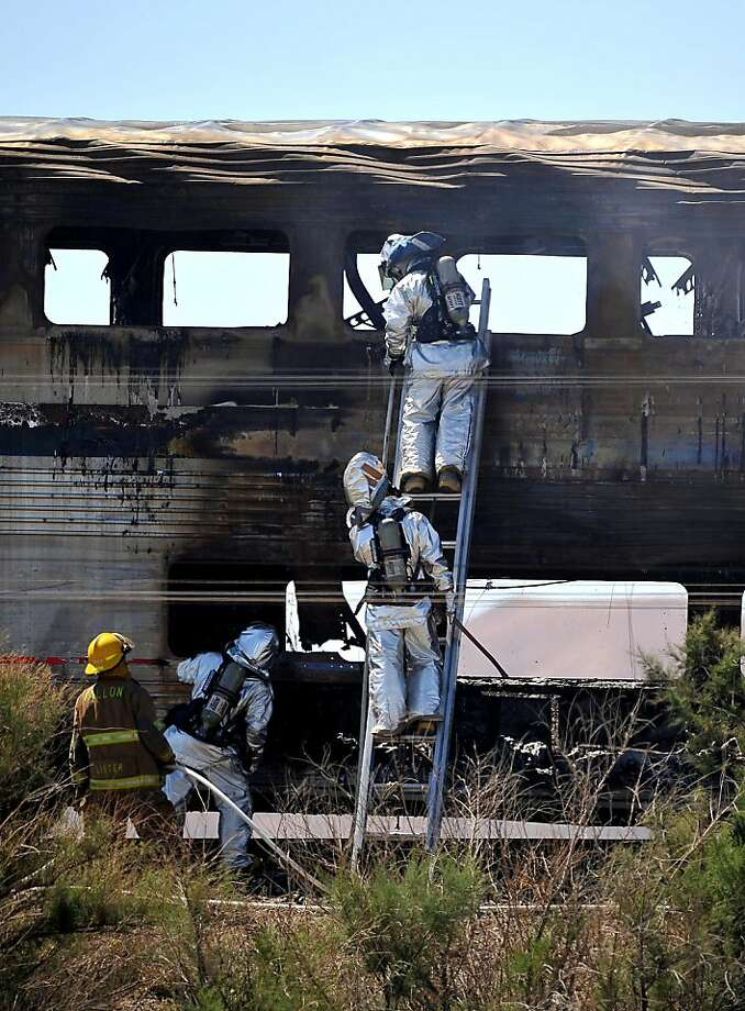Firefighters look at the wreckage of an Amtrak passenger car Friday June 24, 2011 near US 95 north of Fallon, Nev. The west-bound train was struck by a semi-truck and burst into flames.  The driver and a passenger of the truck were killed.  Injured trainppassengers were taken to local hospitals but officials must let the wreck cool off before they continue their search. Photo: Liz Margerum/RGJ, AP
