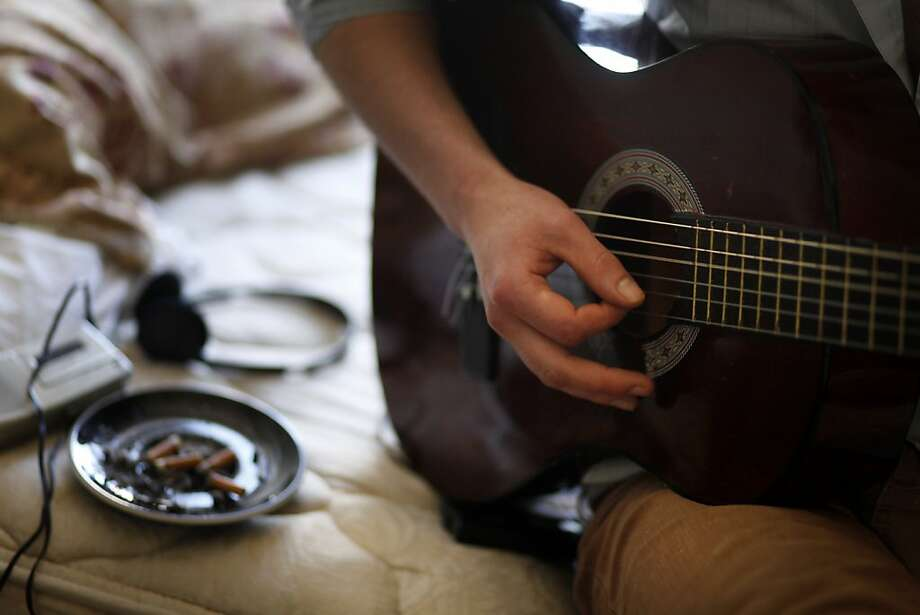 Travis Tribble, 25, works on a new song in his tiny room at the Laguria Hotel in North Beach on Tuesday June 14, 2011 in San Francisco, Calif. Photo: Mike Kepka, The Chronicle