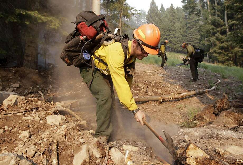 Firefighter Chris Teters, of Portland, Ore., mops up hot spots in Pajarito Mountain ski area near Los Alamos, N.M., Tuesday, June 28, 2011. Firefighters battled a vicious wildfire that was spreading Tuesday through the mountains above the northern New Mexico town that is home to a government nuclear laboratory. Photo: Jae C. Hong, AP