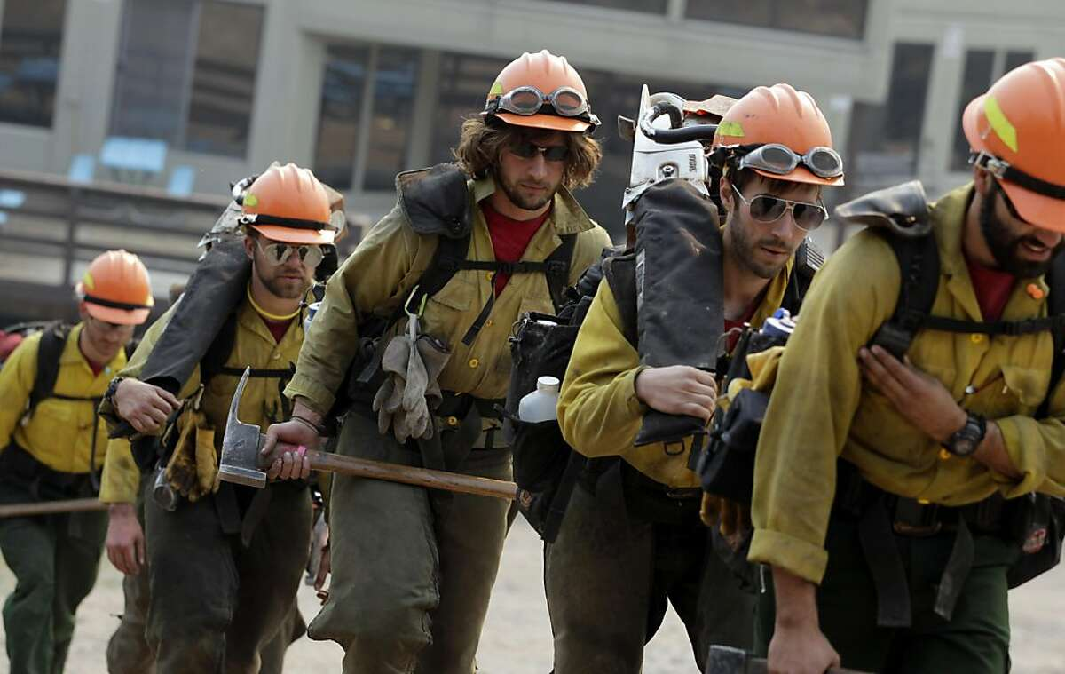 Hotshot crew members walk in line as they prepare to mop up in Pajarito Mountain ski area near Los Alamos, N.M., Tuesday, June 28, 2011. Firefighters battled a vicious wildfire that was spreading Tuesday through the mountains above the northern New Mexicotown that is home to a government nuclear laboratory.