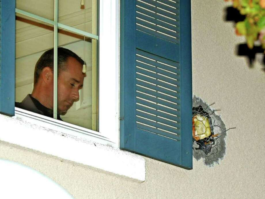 "A Dublin Police officer stands near the exit hole of a cannonball in the second story wall after it traveled through the home in Dublin, Calif., on Tuesday, Dec. 6, 2011. The cannonball was misfired during the taping of an episode of the Discovery Channel show ""MythBusters"" at the Alameda County Bomb Disposal Range. Sheriff's spokesman J.D. Nelson told the Contra Costa Times (http://bit.ly/umCZnD ) that no one was injured and the home's residents didn't even wake up until the dust was settled _ literally on top of them.  (Doug Duran/Staff) Photo: AP"