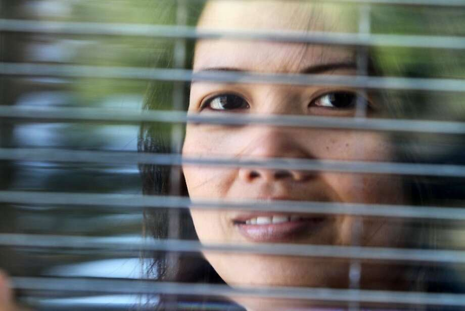 Cecilia Militar is seen through a section of Pythagoras Solar window in San Mateo, Calif. on Friday, June 24, 2011. The double-paned windows generate electricity through horizontal rows of solar cells between the two panes. Photo: Mathew Sumner, Special To The Chronicle