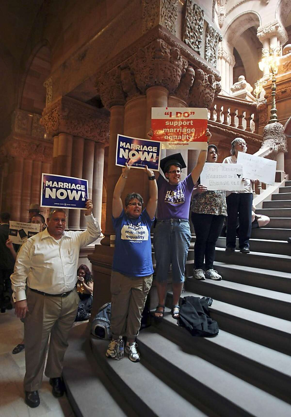 Gay marriage supporters and opponents hold signs in a hallway at the Capitol in Albany, N.Y., on Friday, June 24, 2011. Following the latest marathon session on Thursday, the Senate Republican majority plans to again take up a gay marriage bill that couldbe pivotal moment in the national gay rights movement.