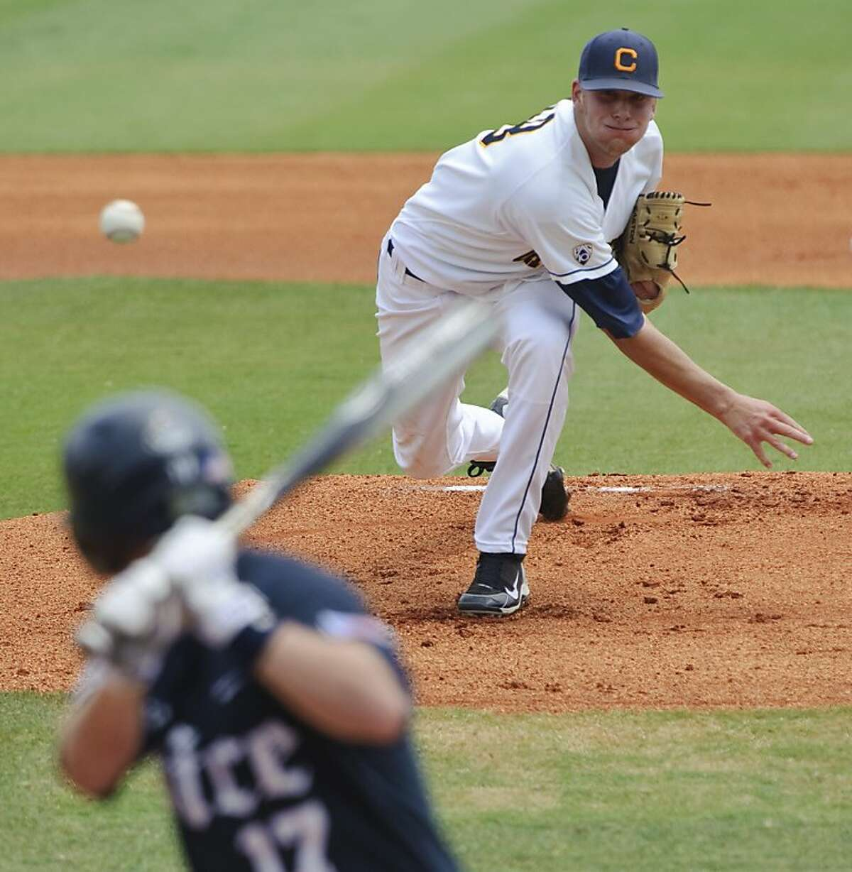 California's Dixon Anderson, back right, delivers a pitch to Rice's Keenan Cook, front left, in the first inning of an NCAA regional college baseball game, Sunday, June 5, 2011, in Houston.