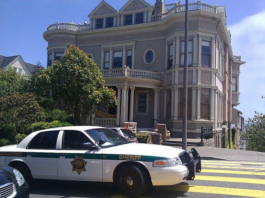 A sheriff's car and furniture outside the mansion at Pacific Avenue and Divisadero Street, where the occupants, Peter and Polly St. Geme, were evicted on June 22, 2011. Photo: Chronicle Staff, Xx