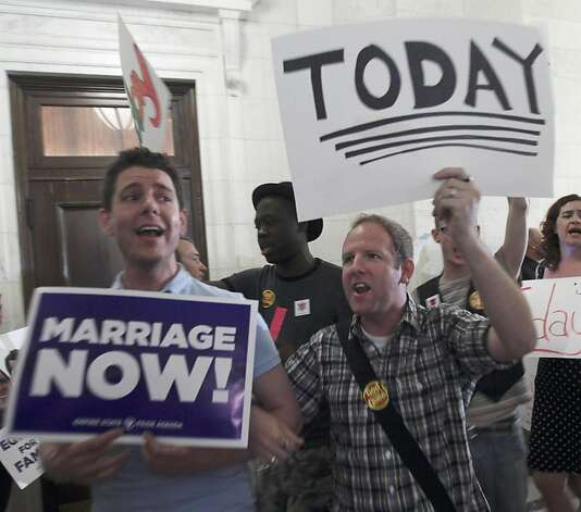 Supporters for gay marriage carry signs and sing in a hallway outside a Republican conference room at the Capitol in Albany, N.Y., on Wednesday, June 22, 2011. Protection for religious groups is the last major issue to be worked out in Wednesday's negotiations over a bill that would legalize same-sex marriages in New York state. Photo: Mike Groll, AP