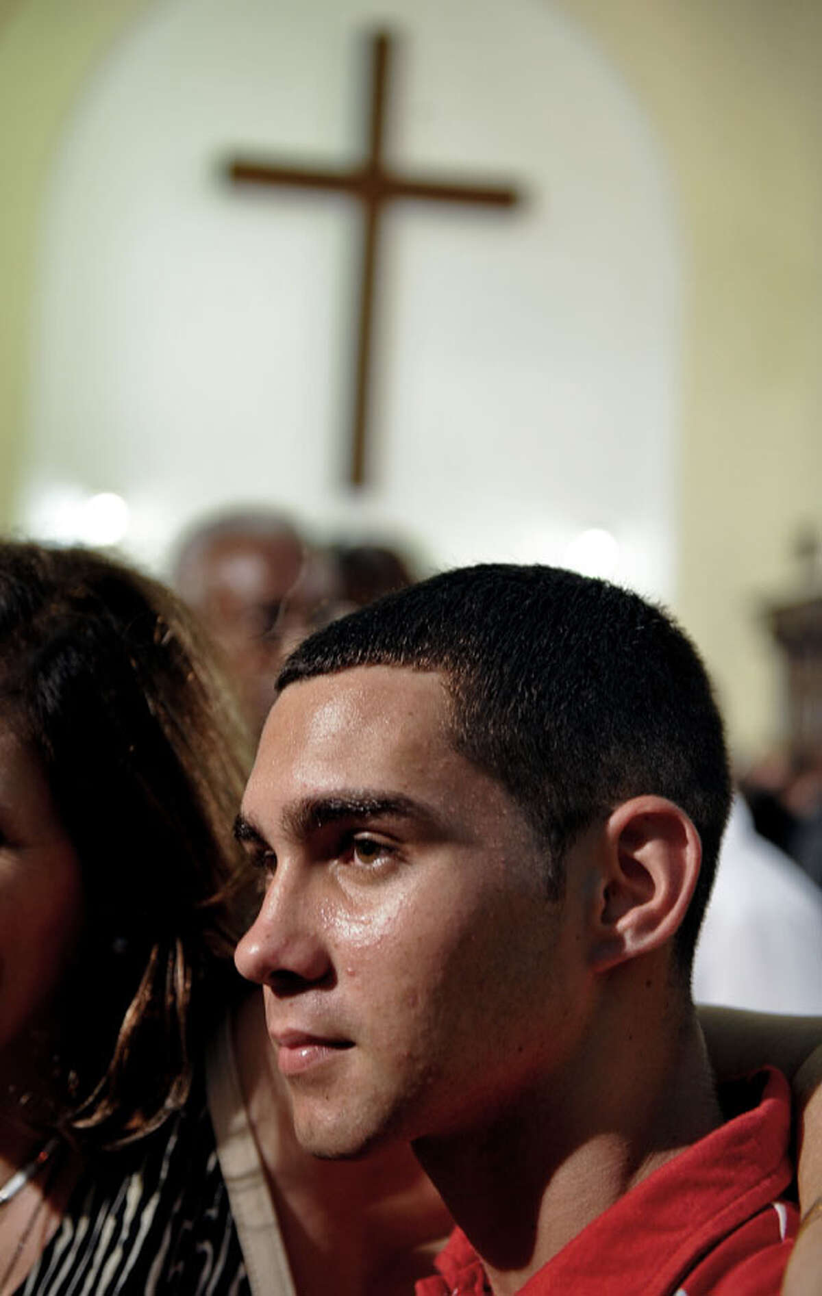 Cuban rafter-boy Elian Gonzalez (R), on June 30, 2010 in a church of Havana, during the celebration of 10th Anniversary of his return from Miami. AFP PHOTO/ADALBERTO ROQUE