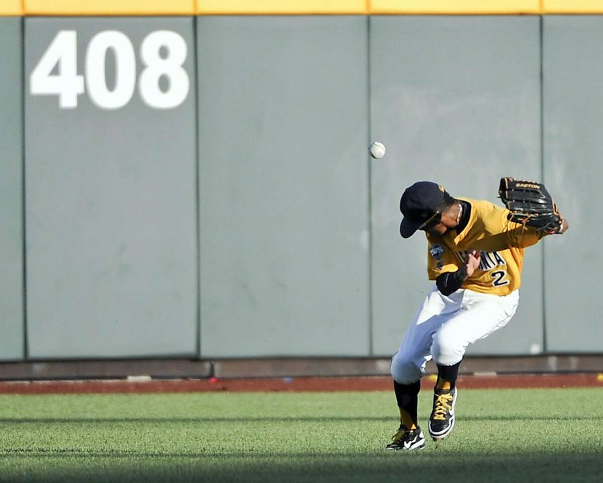 California center fielder Darrel Matthews commits a three-base error on a single by Virginia's Kenny Swab in the sixth inning of an NCAA College World Series elimination baseball game in Omaha, Neb., Thursday, June 23, 2011. Swab scored on the play.