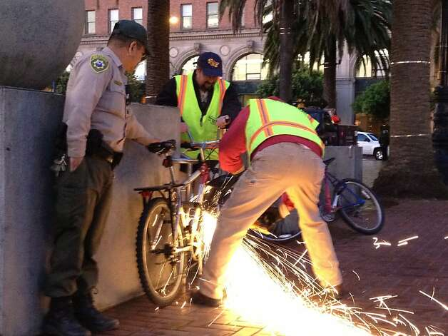City public works crews remove a locked bike at Justin Herman Plaza after police cleared out the Occupy camp before dawn on Wednesday, December 7, 2011. Crews confiscated all the property. Photo: Will Kane, The Chronicle