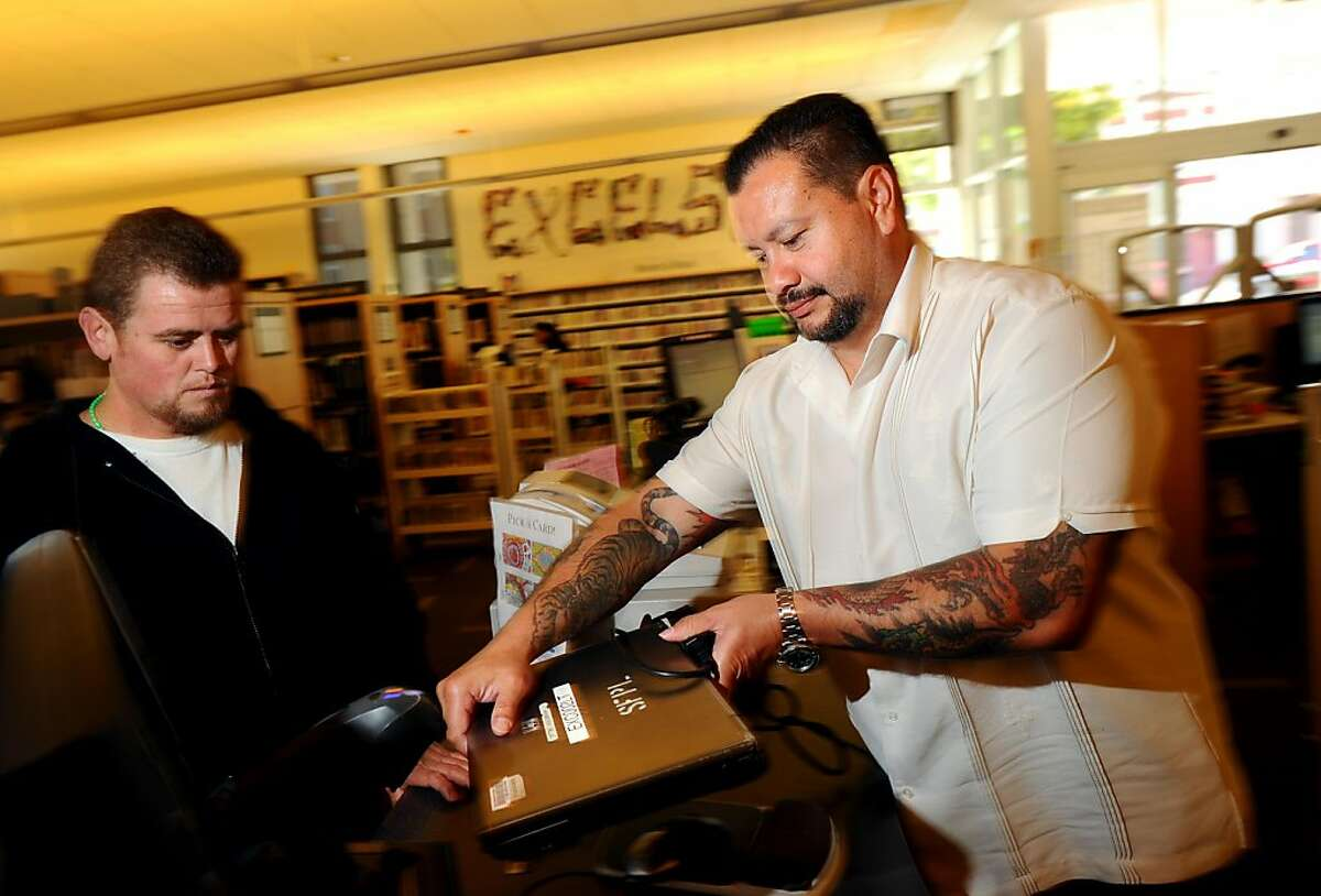 Octavio Ruiz, right, a library technician at the San Francisco Public Library's Excelsior branch, lends a laptop to Ivan Anzueto on Thursday, June 23, 2011, in San Francisco.