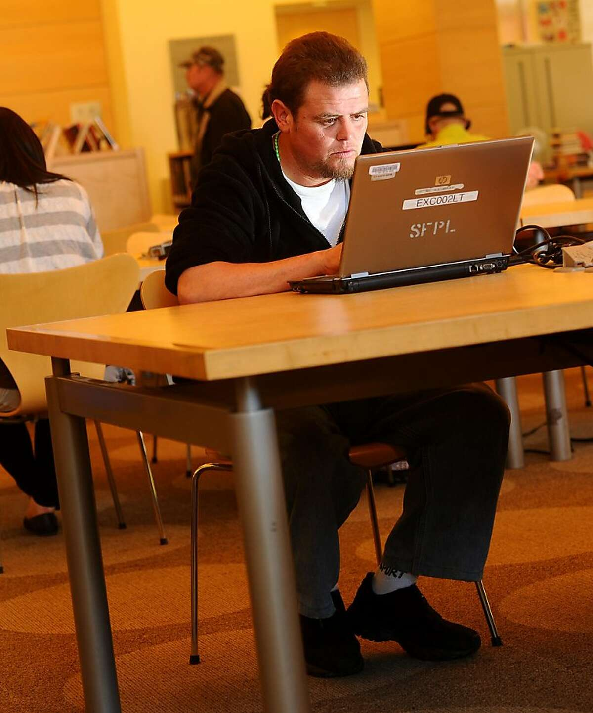 Ivan Anzueto uses a borrowed laptop at the San Francisco Public Library's Excelsior branch on Thursday, June 23, 2011, in San Francisco. Anzueto, who does not have a computer at home, used the laptop to search craigslist for jobs.