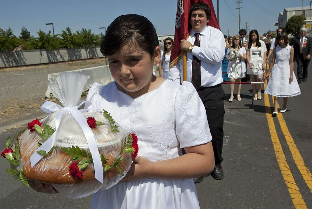 Laura Soares, 9, followed by her brother, Manuel, 16, carries the traditional rosquilha, a sweet bread traditional to the Portuguese island of St. Geogre, in a procession to Five Wounds Portuguese National Church during the Holy Ghost Festa on Sunday, June 12, 2011 in San Jose, Calif. The feast commemorates the patron saint of Portugal, St. Isabel.