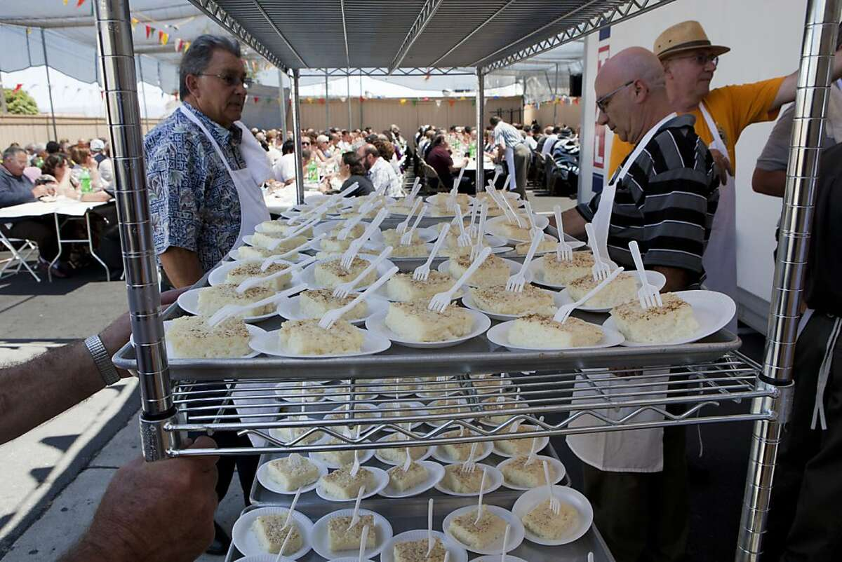 Alberto Dias, left, and Juvenal Nunes, right, prepare to serve the dessert course of rice pudding to hundreds of Bay Area Portuguese Catholics and invited guests during the Holy Ghost Festa at the Aliana Jorgense Hall on Sunday, June 12, 2011 in San Jose, Calif.