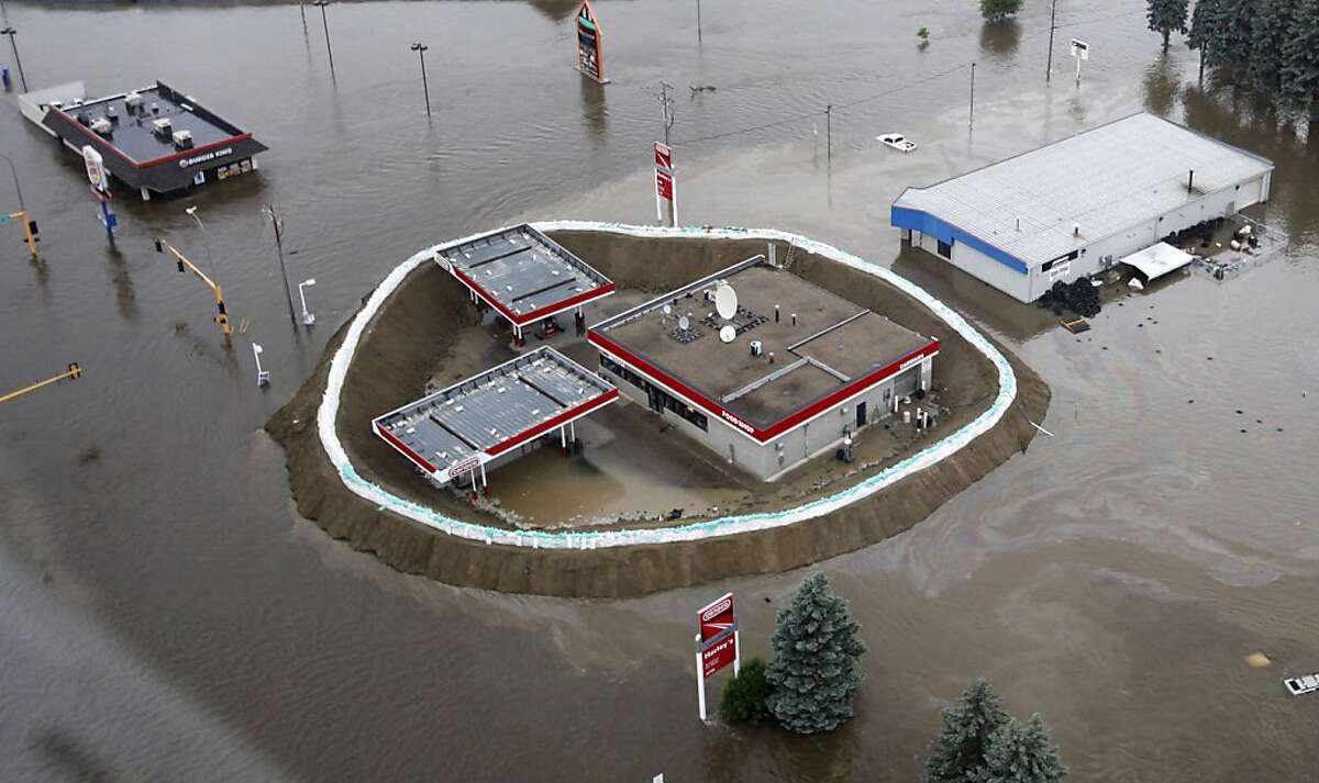 In this aerial photo, a Conoco gas station is surrounded by sand bags, the flood waters of the Souris River, and an oil slick Friday, June 24, 2011 in Minot, N.D. North Dakota Gov. Jack Dalrymple says the Souris River is flowing over most levees in Minotas it surges past a 130-year-old record level.