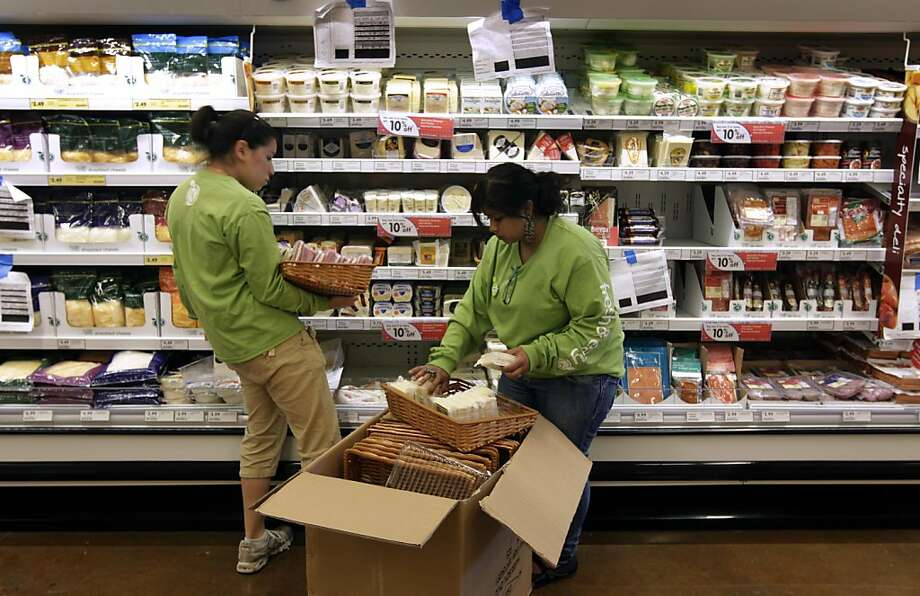 Employees stock the dairy section with cheese at the Fresh & Easy grocery store in the Outer Richmond district of San Francisco, Calif. on Tuesday, June 21, 2011. The new market opens to the public on Wednesday. Photo: Paul Chinn, The Chronicle