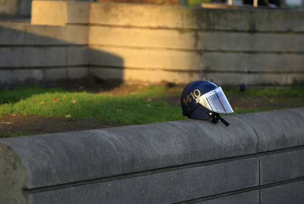 A police officer's riot helmet rests on a ledge while a crew from the Department of Public Works cleans up Justin Herman Plaza after authorities cleared out the Occupy encampment in an early morning raid in San Francisco, Calif. on Wednesday, Dec. 7, 2011. Photo: Paul Chinn, The Chronicle