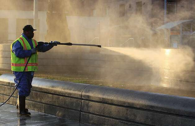 A crew from the Department of Public Works uses a power washer to clean Justin Herman Plaza after police cleared out the Occupy encampment in an early morning raid in San Francisco, Calif. on Wednesday, Dec. 7, 2011. Photo: Paul Chinn, The Chronicle