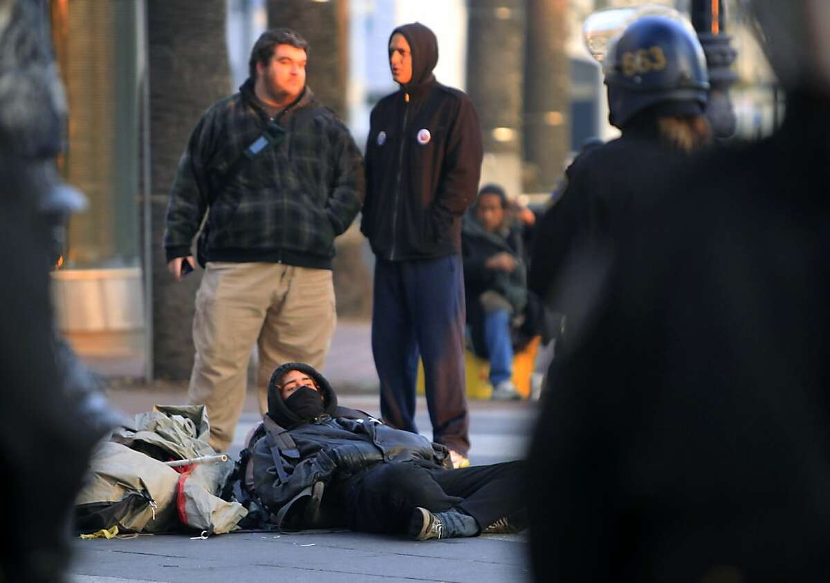 Protesters watch a line of police guard DPW workers cleaning up after authorities cleared out the Occupy encampment at Justin Herman Plaza in an early morning raid in San Francisco, Calif. on Wednesday, Dec. 7, 2011.