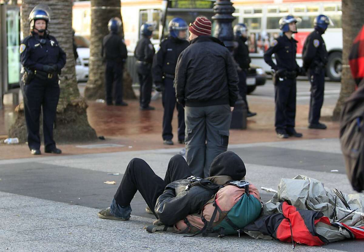 Displaced occupiers watch a line of police guard DPW workers cleaning up after authorities cleared out the Occupy encampment at Justin Herman Plaza in an early morning raid in San Francisco, Calif. on Wednesday, Dec. 7, 2011.