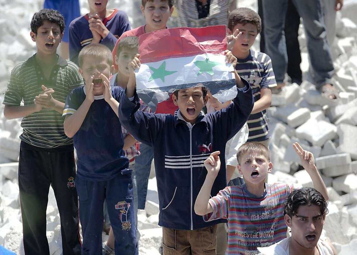 Syrian refugee children hold a hand made Syrian flag during a protest against Syrian President Bashar Assad's speech in a refugee camp in Yayladagi, Turkey, Monday, June 20, 2011. Syria's embattled president said Monday his regime would consider politicalreforms, including ending his Baath Party's monopoly in politics, as he clings to power in the face of a growing, nationwide protest movement that refuses to die.The opposition dismissed Bashar Assad's speech, saying it lacked any clear sign of a transition to true democracy.