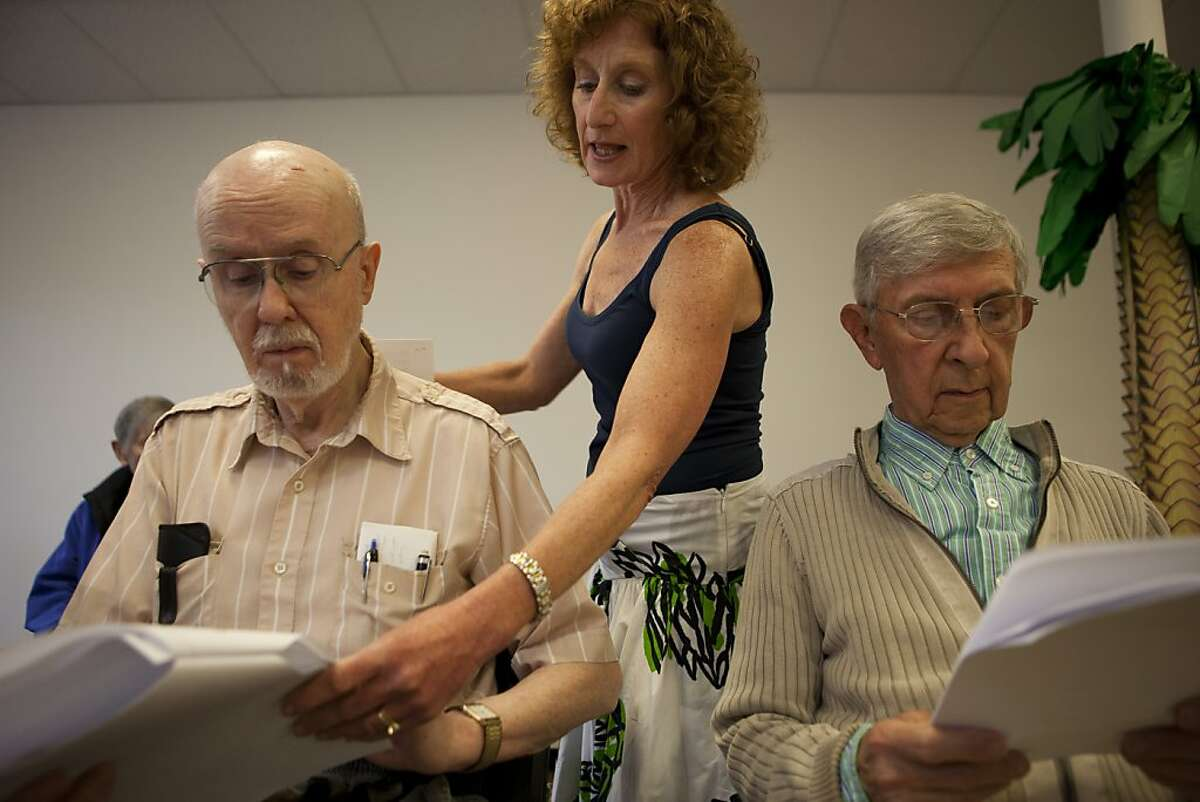Speech Pathologist Randy Hoffman monitors the progress of patients Knud Knudsen, left, of Palo Alto, and Wence Coron of Santa Clara, during a choir session for patients with Parkinson's at the Parkinson's Institute on Thursday, June 16, 2011 in Sunnyvale, Calif. Singing helps strengthen the throat muscles of Parkinson's patients which betters their ability to speak and swallow.