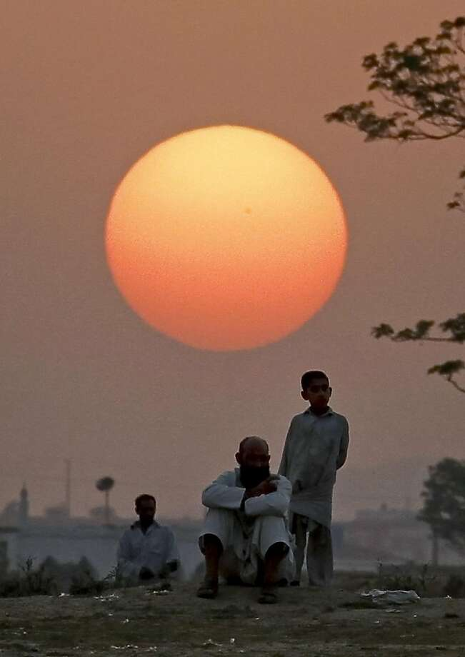 Afghan refugees are silhouetted against sunset while they watch youths playing cricket at a slum on the outskirts of Islamabad, Pakistan, Sunday, June 19, 2011. Photo: Anjum Naveed, AP