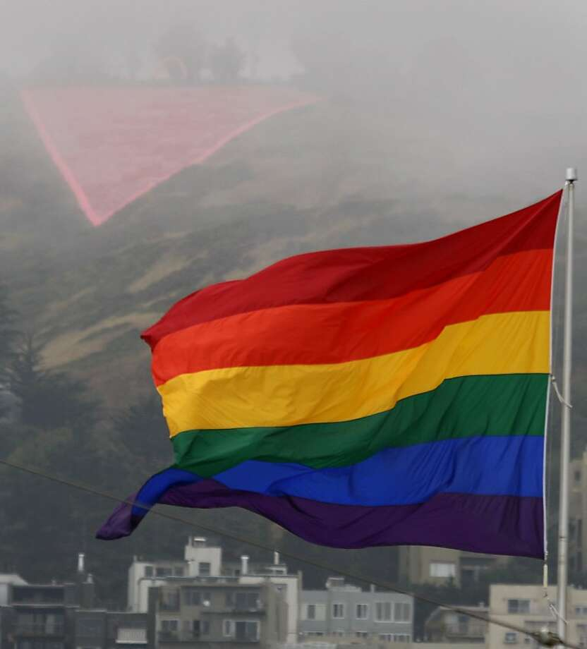 The gay pride flag flies at Market and Castro Streets in front of the large pink triangle, shrouded in fog, on Twin Peaks in San Francisco, Calif., on Saturday, June 28, 2008. Photo by Paul Chinn / The Chronicle Photo: Paul Chinn, The Chronicle