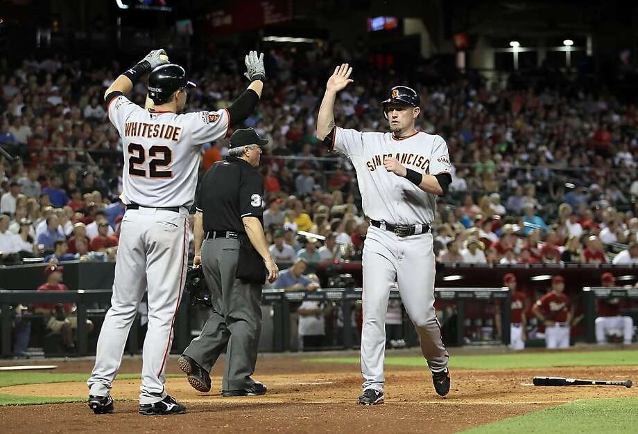 Aubrey Huff #17 of the San Francisco Giants high fives Eli Whiteside #22 after Huff scored a run against the Arizona Diamondbacks during the sixth inning of the Major League Baseball game at Chase Field on June 15, 2011 in Phoenix,Arizona. Photo: Christian Petersen, Getty Images