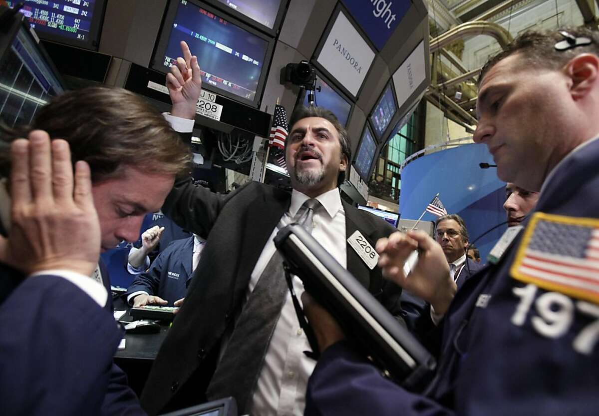 Specialist Jason Blatt, center, calls out prices for Pandora internet radio as it begins trading on the floor of the New York Stock Exchange Wednesday, June 15, 2011.