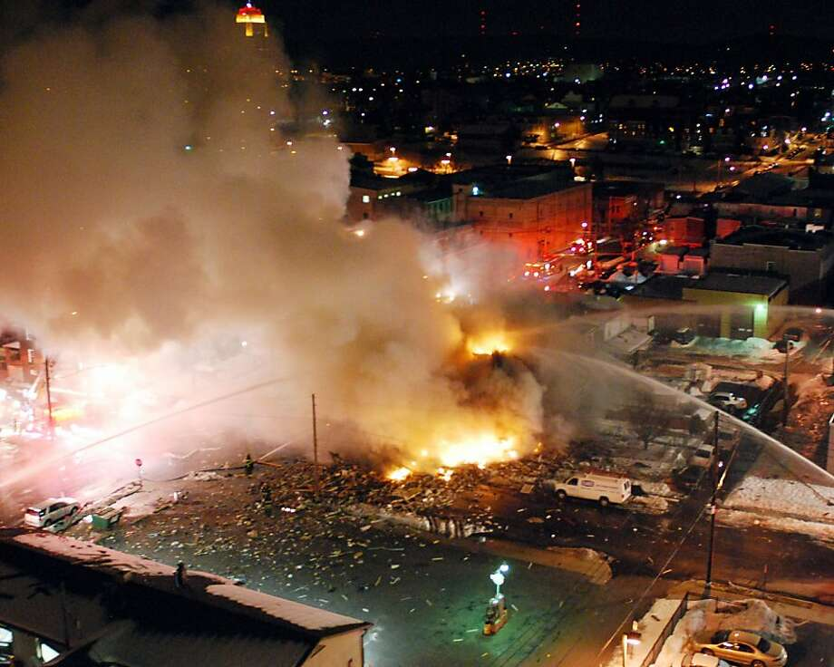 In this Feb. 9, 2011 photo, emergency crews respond to a massive explosion in a residential neighborhood of downtown Allentown, Pa. The natural gas explosion in Allentown killed at least one person, leveled two houses, spawned fires that burned for more than seven hours and prompted the evacuation of hundreds of people. At least five others were unaccounted for Thursday. (AP Photo/Express-Times, Chris Post) NO SALES Photo: Chris Post, ASSOCIATED PRESS