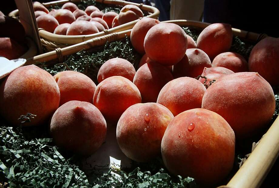 Peaches glow in the morning sunlight at the Ferry Plaza Farmers Market. Photo: Paul Chinn, The Chronicle
