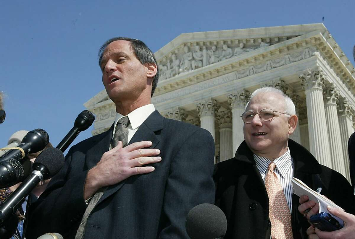 Michael Newdow, left, a California atheist who challenged the Pledge of Allegiance on behalf of his daughter, meets reporters outside the Supreme Court in Washington Wednesday, March 24, 2004, after a hearing before the court. Newdow told the court that the words