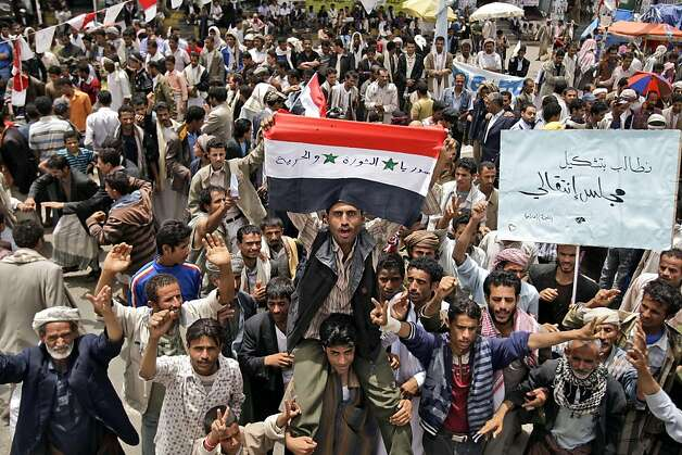 "An anti-government protestor, center, holds a Syrian flag that reads in Arabic, ""Syria, revolution, and freedom"", during a demonstration demanding the resignation of Yemeni President Ali Abdullah Saleh, in Sanaa, Yemen, Tuesday, June 14, 2011. A senior Yemeni official in the Saudi capital says President Ali Abdullah Saleh has developed a problem with his throat but that his overall condition is stable. Arabic reads on the placard right, "" We demand the formation of a transitional council"". (AP Photo/Hani Mohammed) Photo: Hani Mohammed, AP"