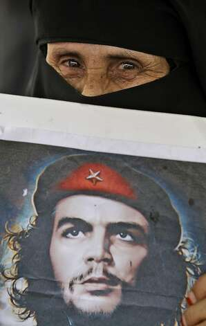 A female anti-government protestor holds a poster showing Argentine-born Cuban revolutionary Ernesto 'Che' Guevara, during a demonstration demanding the resignation of Yemeni President Ali Abdullah Saleh, in Sanaa, Yemen, Tuesday, June 14, 2011. A senior Yemeni official in the Saudi capital says President Ali Abdullah Saleh has developed a problem with his throat but that his overall condition is stable. Photo: Hani Mohammed, AP