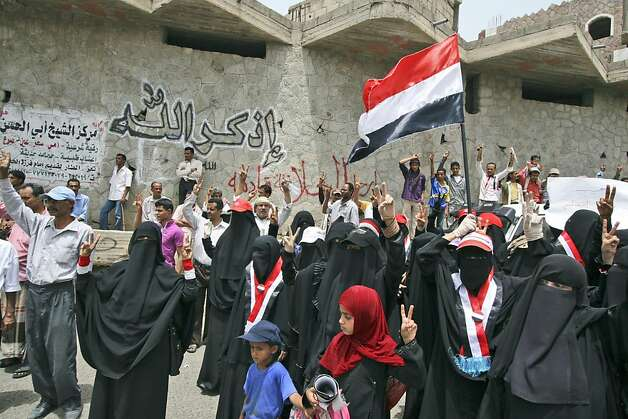 "Anti-government protestors chant slogans during a demonstration demanding the resignation of Yemeni President Ali Abdullah Saleh, in Taiz, Yemen, Tuesday, June 14, 2011. A senior Yemeni official in the Saudi capital says President Ali Abdullah Saleh hasdeveloped a problem with his throat but that his overall condition is stable. Arabic reads on the wall in the background, ""Mention God"". Photo: Anees Mahyoub, AP"