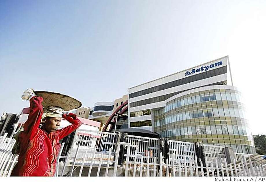 A laborer walks in the backdrop of the office of Satyam Infocity, the office of Satyam Computer Services Ltd., in Hyderabad, India, Wednesday, Jan. 7, 2009. The chairman of India's Satyam Computer Services Ltd. quit Wednesday after admitting the company's profits had been doctored for several years, shaking faith in the country's corporate giants as shares of the software services provider plunged nearly 80 percent. (AP Photo/Mahesh Kumar A.) Photo: Mahesh Kumar A, AP