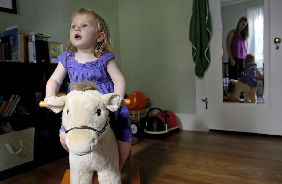 Suzanne Galvin watches her daughter Lily play our her rocking horse in Lily's own room at their new home, Wednesday June 15, 2011, in Oakland, Calif. Their family moved from the city to Oakland a few months ago, because of the schools, weather and the cost on housing.