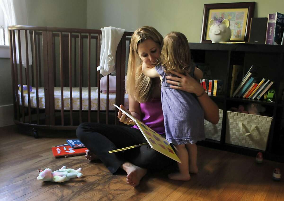 Suzanne Galvin gets a hug from her daughter Lily after they read together, Wednesday June 15, 2011, in Oakland, Calif