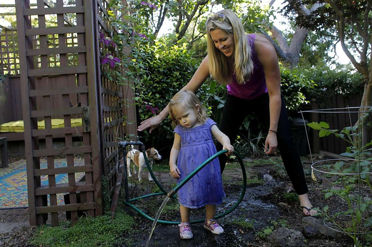 Suzanne Galvin plays with her daughter Lily as they water the plants in their backyard, Wednesday June 15, 2011, in Oakland, Calif. Their family moved from the city to Oakland a few months ago, because of the schools, weather and the cost on housing.