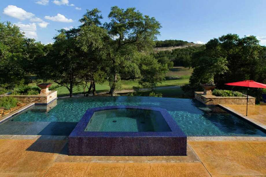 Built with a commanding view of the Cedar Creek golf course off Kyle Seale Parkway north of Loop 1604, this pool has a dramatic 35-foot negative edge that gives the appearance that the water is spilling out. Builders note that they are seeing an increased interest in pools with such fancy features among their high-end clients. Photo: COURTESY PHOTO / Photo courtesy of Blue Haven Pools