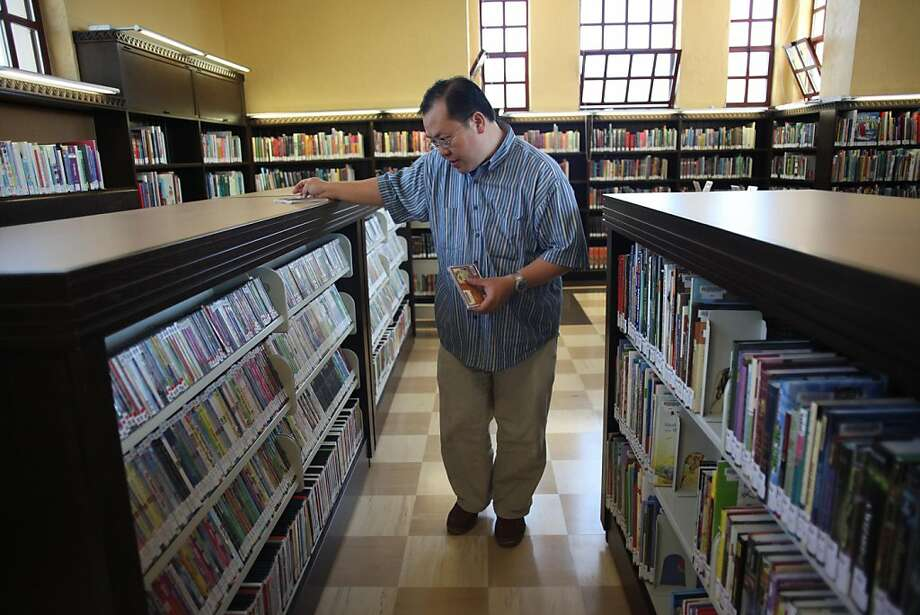 Eric Auyeung, library assistant, puts books on shelves at the renovated Anza Branch Library on Wednesday, June 15, 2011 in San Francisco, Calif. The Anza Branch Library reopens to the public on Saturday, June 18, 2011. Photo: Lea Suzuki, The Chronicle