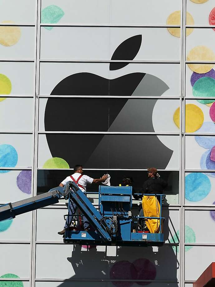 SAN FRANCISCO, CA - FILE:  Workers apply the Apple logo the outside of the Yerba Buena Center for the Arts on February 28, 2011 in San Francisco, California.  According to reports April 5, 2011, NASDAQ OMX announced it would rebalance on May 2, 2011, cutting Apple's weighting on the NASDAQ 100 index. Photo: Justin Sullivan, Getty Images