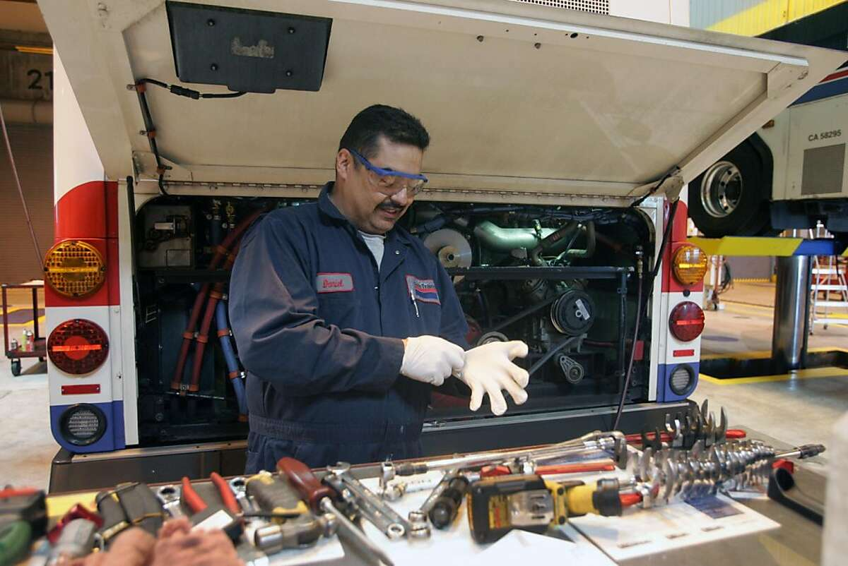 Mechanic Daniel Jimenez gloves up to resume work at SamTrans' north base on Thursday, June 16, 2011 in South San Francisco, Calif. The San Mateo County bus service hosted a tour of its facilities in recognition of National Dump the Pump Day to encourage people to use public transportation instead of their cars.