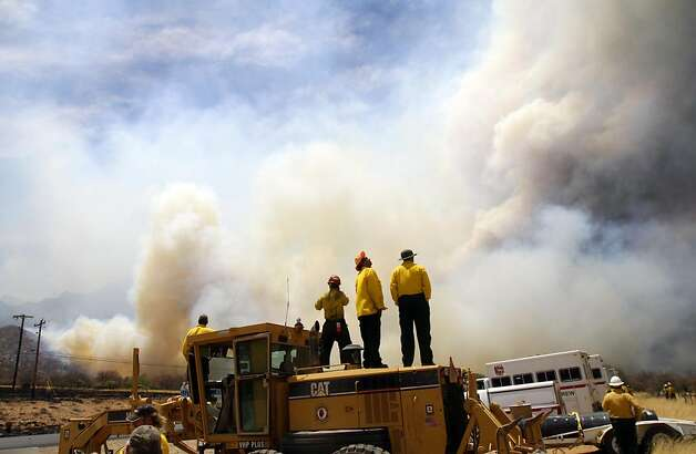 Fire crews watch the wildfire as it crosses Arizona 92 around 1 p.m. Thursday afternoon, June 16, 2011, after it burned through Stump Canyon area near Hereford, Ariz. Photo: David Sanders, AP